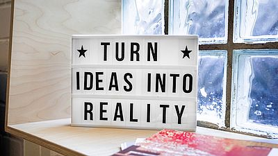 "Foto: Motivationstafel mit Schriftzug ""Turn ideas into reality"""