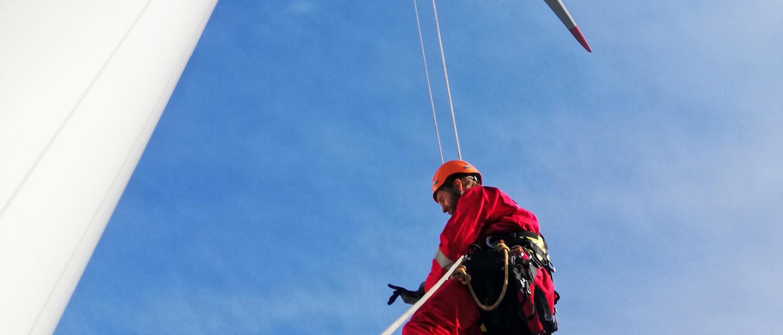Foto: Industriekletterer hängt an Seil und arbeitet an Windkraftanlage