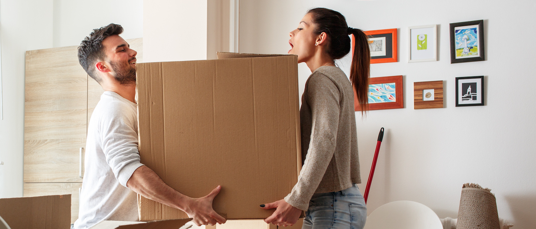 Foto: Paar schleppt Umzugskarton in Wohnung